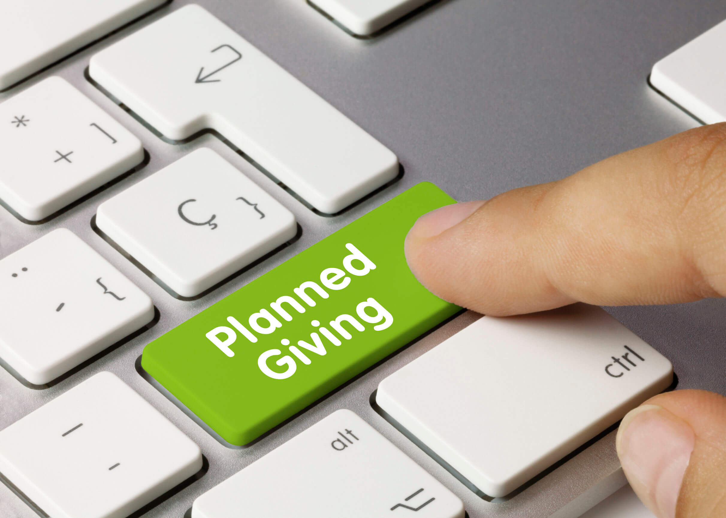 """Image of a computer keyboard with a """"planned giving"""" button, representing how estate planning and charitable giving attorney Anna M. Price helps clients with planning charitable giving in the context of overall estate planning."""