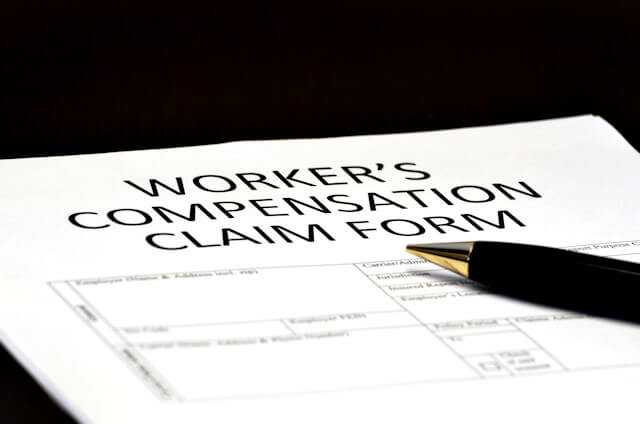 Image of a worker's compensation claim form and a pen, representing how WV workers' compensation defense attorney Steve Wellman and his team help clients understand workers' compensation matters like the changing requirements regarding WV Form WC-1.