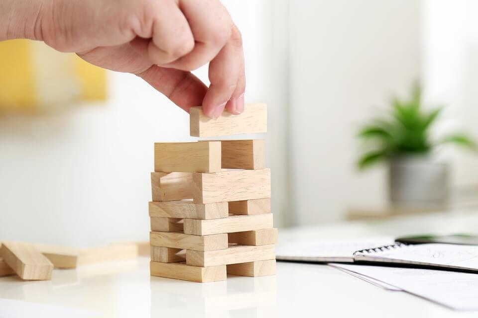 Image of a person stacking wooden blocks, representing how an experienced hospitality attorney like Xavier W. Staggs can guide you on the importance of evaluating various hospitality business structures before choosing one for your business.