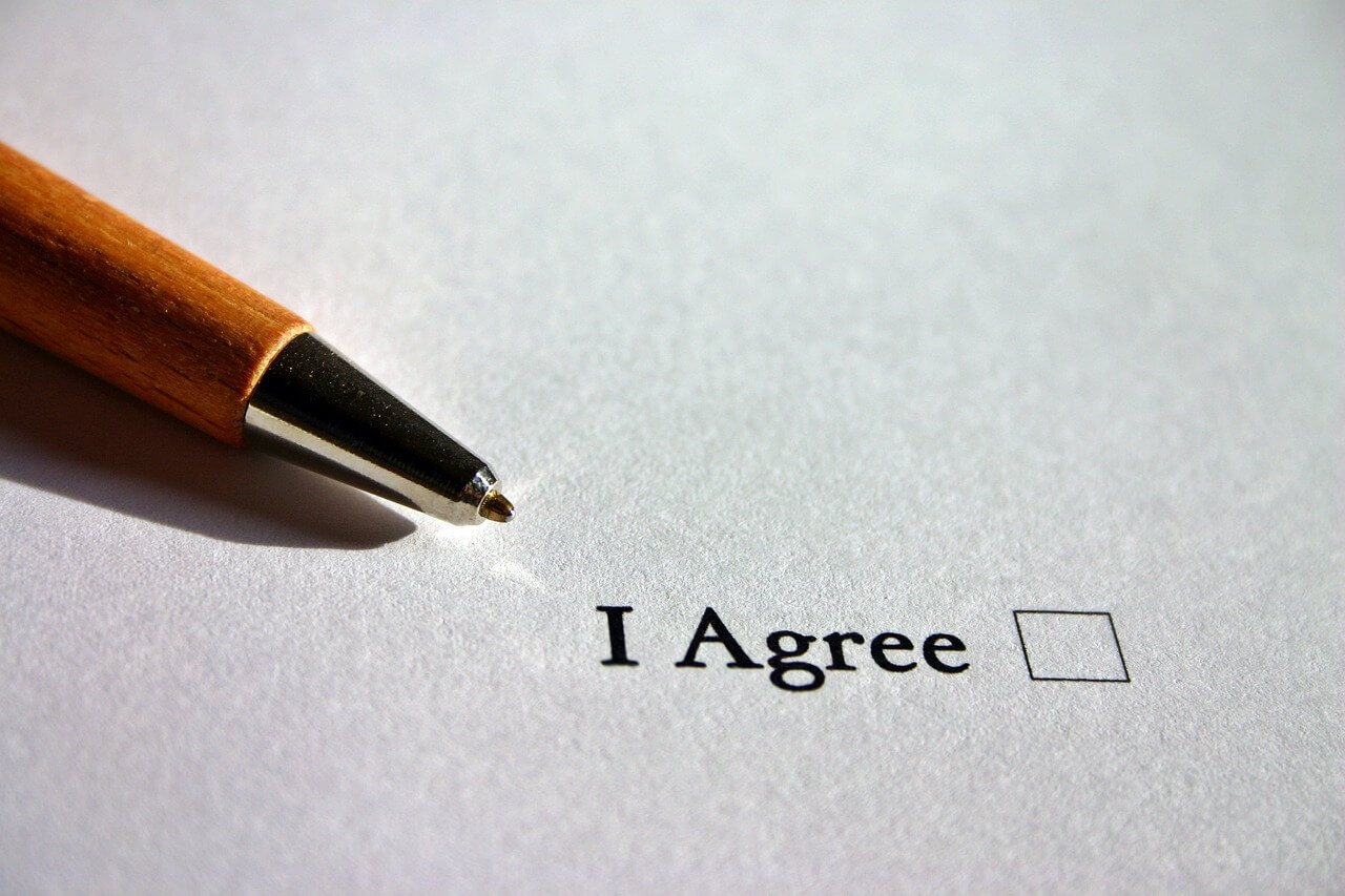 "An image of a pen and a checkbox that reads ""I agree,"" representing the risks for employers and others who enter into agreements that do not comply with the WV workers' compensation fee schedule and how experienced workers' compensation attorneys like Steven K. Wellman at Jenkins Fenstermaker, PLLC can help employers and insurers navigate WV workers' compensation law."