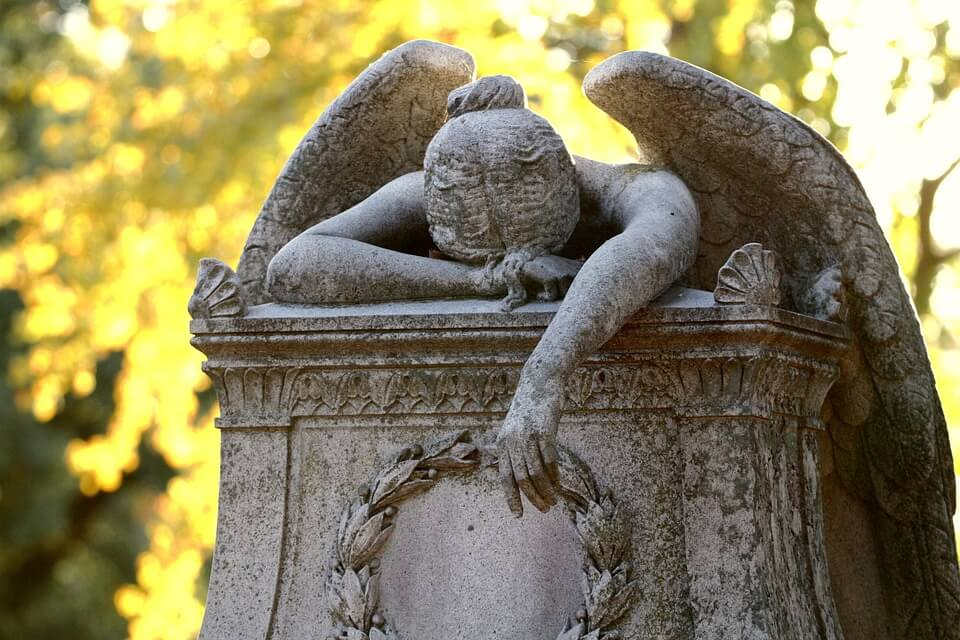 An image of a stone angel weeping on a headstone, representing the loss of a loved one and the burden placed on loved ones who must pay the Kentucky inheritance tax.