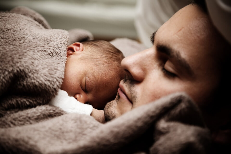Photo of an infant and father, who can rest easy because he completed his deportation estate planning with the help of Anna M. Price at Jenkins Fenstermaker, PLLC.