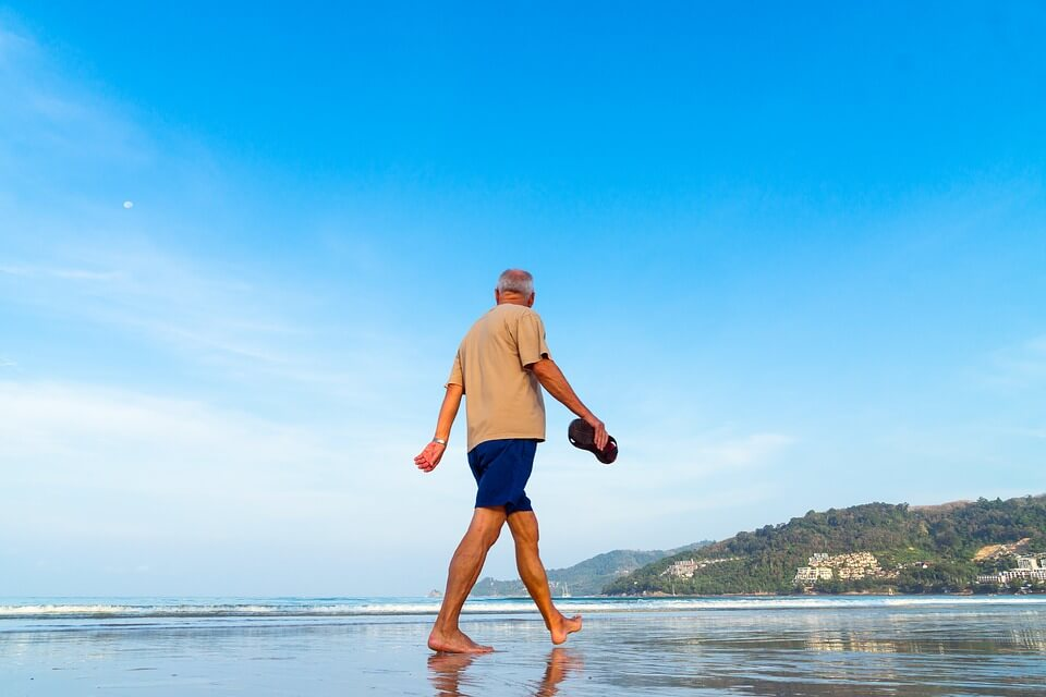 Image of a senior man walking on the beach, representing the need to include Medicare and Medicaid in your estate plan and how an experienced West Virginia (WV) estate planning attorney like Anna M. Price can help.