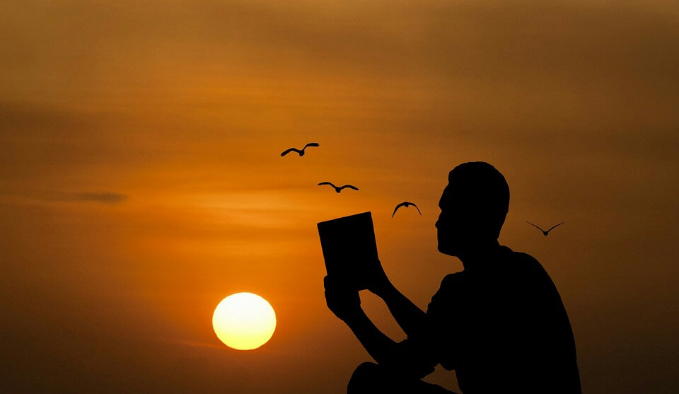 Image of a silhouetted person reading at sunset, representing how attorney Oscar R. Molina can help nonimmigrant students can obtain a US student visa to study at a West Virginia university.
