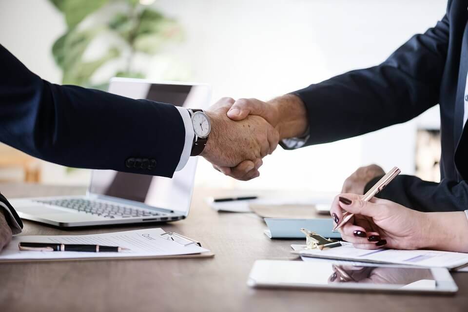 Image of two people in suits shaking hands in a meeting depicting that the client's product is covered with products liability and Toxic Tort.
