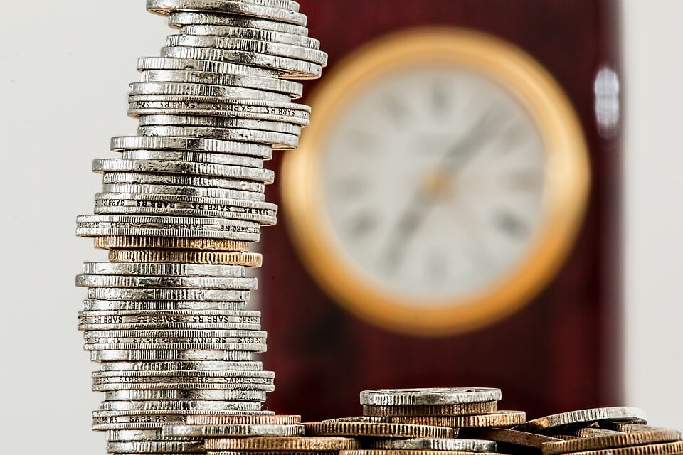 An image of a stack of coins with a clock in the background, representing how attorney Anna M. Price of Jenkins Fenstermaker can show you the benefits of advance planning for Medicaid asset protection in WV, KY, and OH.