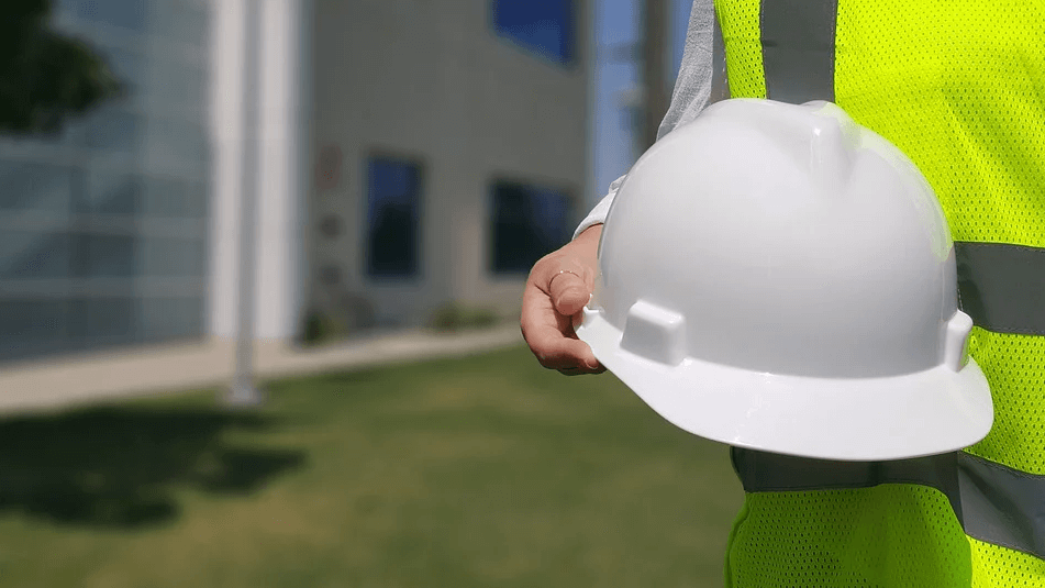 Image of a man wearing a safety vest and holding a hard hat, representing the impact of the West Virginia right to work law on employees, employers, and unions.