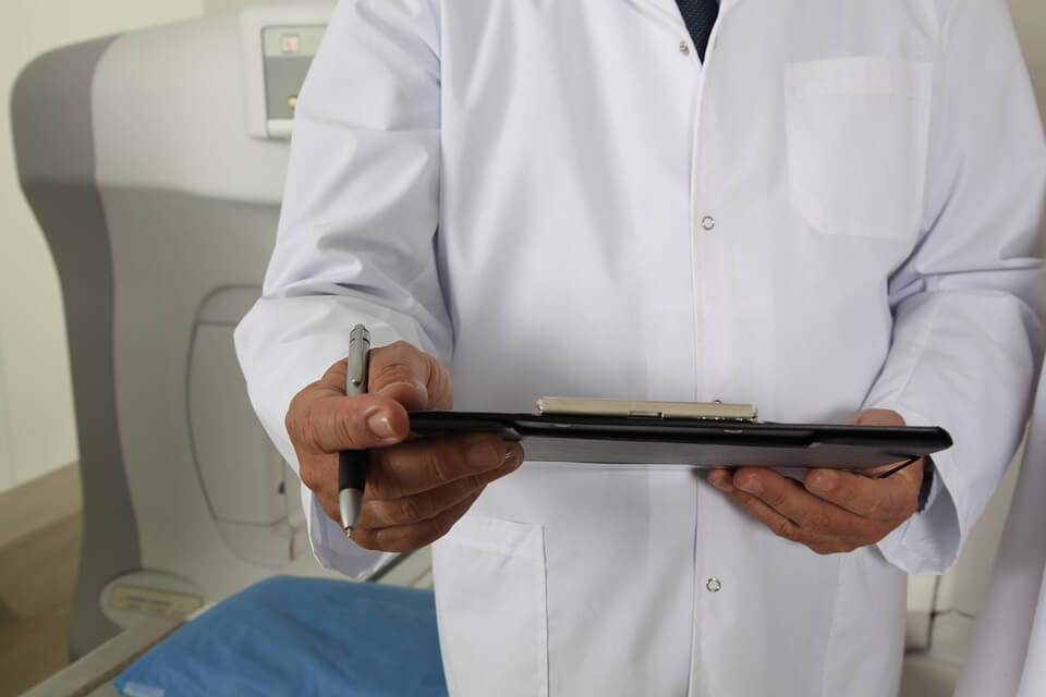 Image of a doctor with a clipboard depicting insurance coverage.