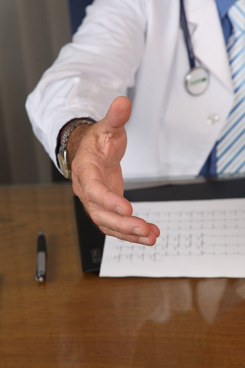 Image depicting a doctor at a desk explaining Malpractice Defense.