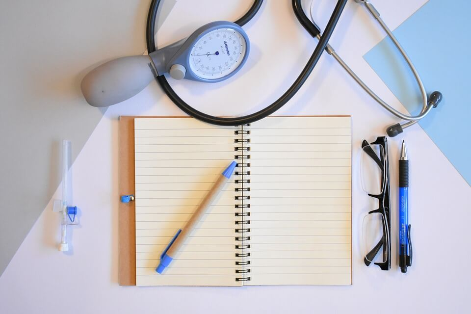 Image of a notepad, glasses, pen, and stethoscope, representing some of the tools needed for someone planning to open a nurse practitioner independent practice in WV.