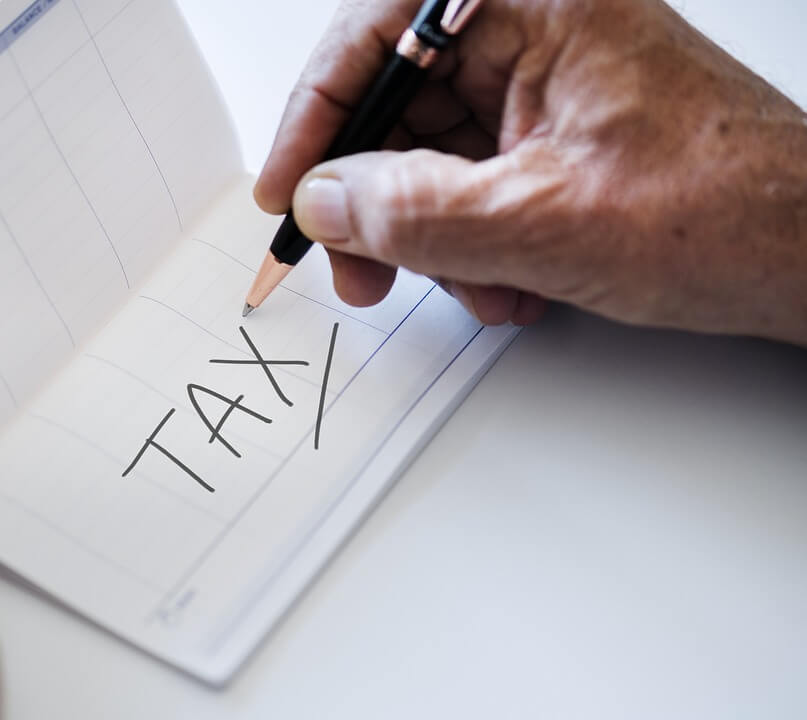"An image of a man writing the word ""tax,"" representing the need to use estate tax planning techniques to ensure your transfer of wealth after death is maximized."