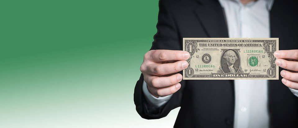 Image of  small business owner holding a dollar bill, representing how the WV Small Business Capital Act helps small businesses use funding from sources close to home.