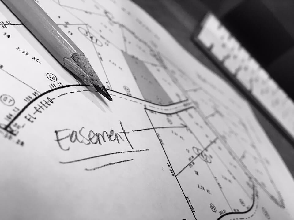 """Image of property lines on paper with the word """"easement,"""" representing the potential for commercial real estate disputes in WV and how a WV commercial real estate attorney at Jenkins Fenstermaker PLLC can help."""