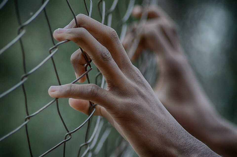 Image of a man's hands holding onto a prison fence, representing the question asked by many employers,
