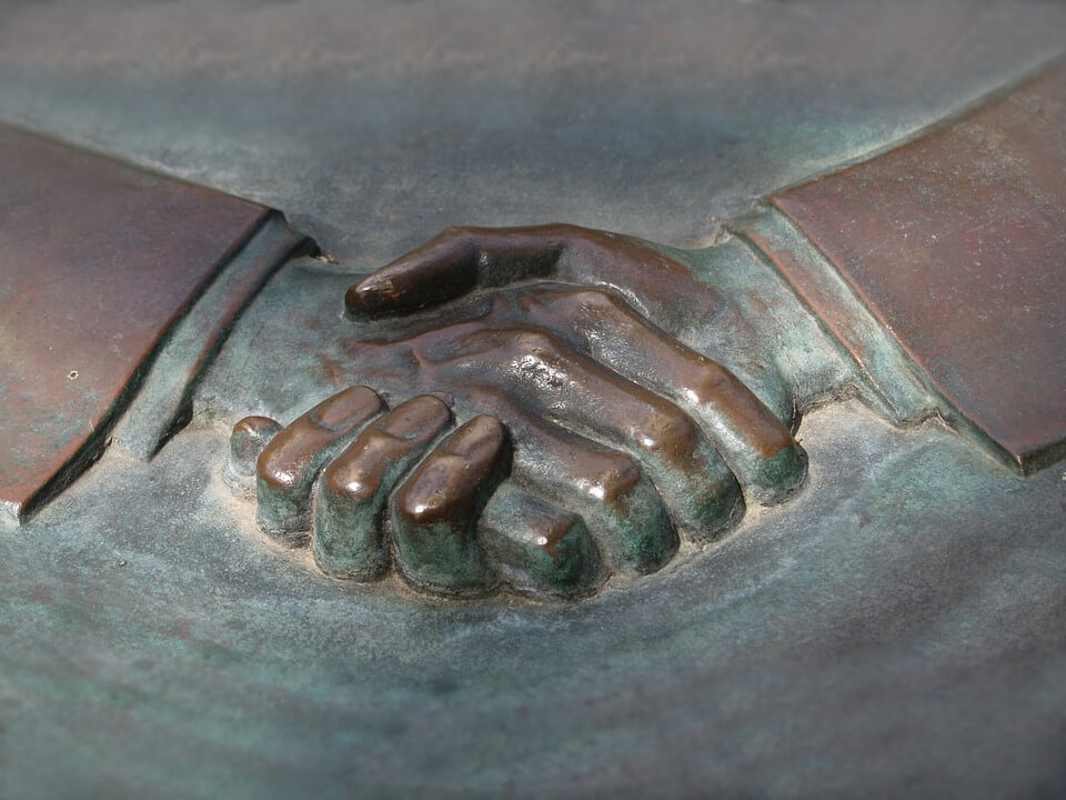 An image of a relief sculpture of hands shaking, representing the permanent nature of a business deal and how a WV mergers and acquisitions lawyer from Jenkins Fenstermaker can help you avoid mistakes.
