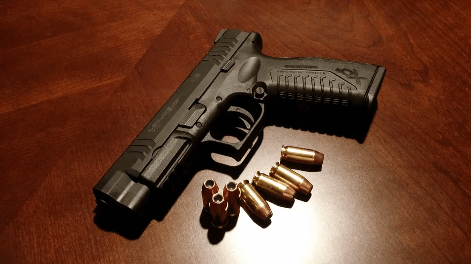 An image of a handgun and ammunition, representing the need for gun owners to know gun license reciprocity and concealed carry laws, especially when traveling through or to other states, even if they've planned ahead with a gun trust.