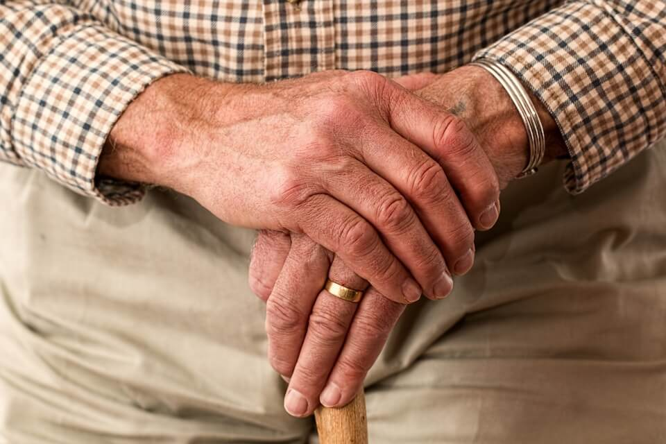 A close-up image of the hands of an older man holding a walking stick, representing the need for elder care planning in WV, KY, and OH and how an experienced attorney for long-term care planning can help.