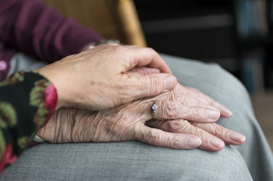 Image of a young person's hand holding an older woman's hand, representing how Ohio guardianship lawyer Anna Price helps guardians and wards through proceedings regarding adult guardianship in Ohio.