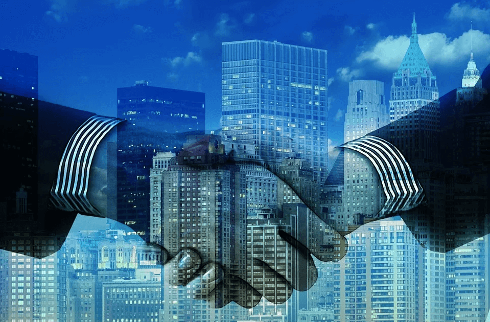 Image of a handshake in front of a cityscape, representing how Xavier W. Staggs can help your business planning and share his M&A outlook for 2021.