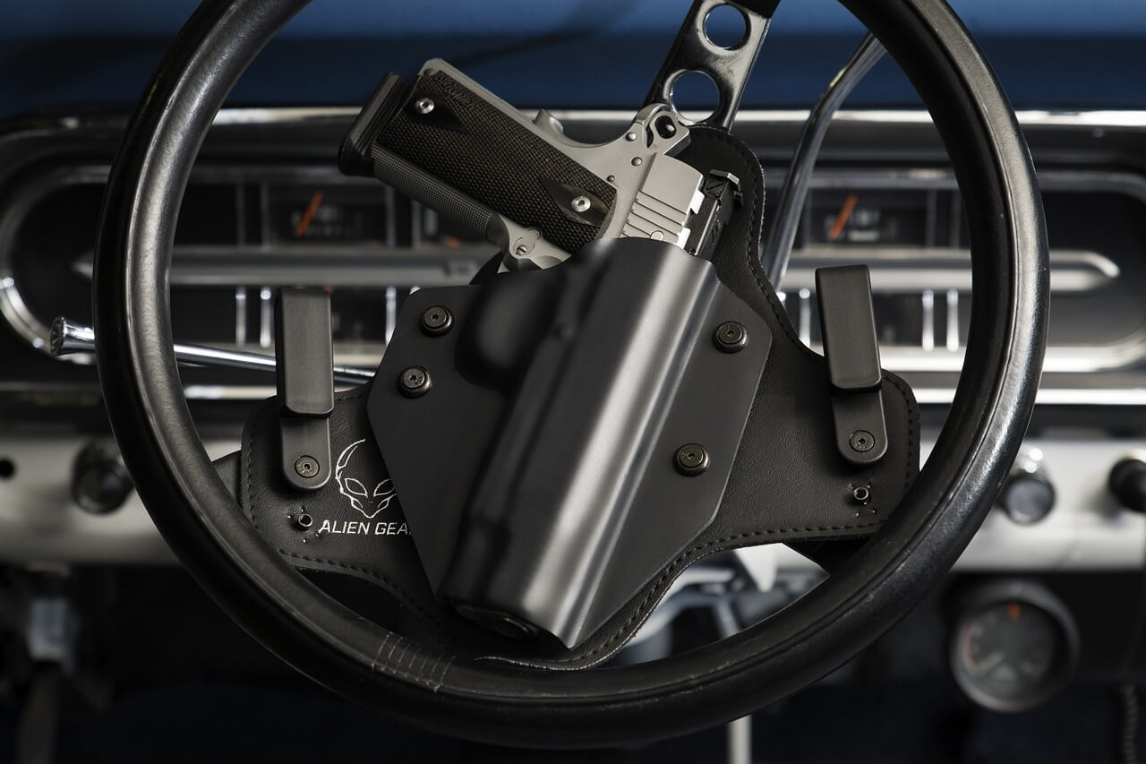 An image of a handgun attached to a vehicle's steering wheel, representing recent developments in WV gun laws for businesses in vehicles in parking lots and how attorney Stephen J. Golder can help you understand how these laws affect your business.