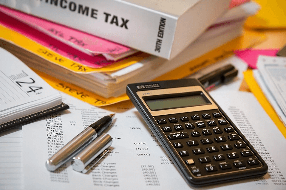 Image of a calculator next to tax records and files, representing how West Virginia employer lawyers at Jenkins Fenstermaker help employers navigate the FFCRA paid leave tax credit requirements.