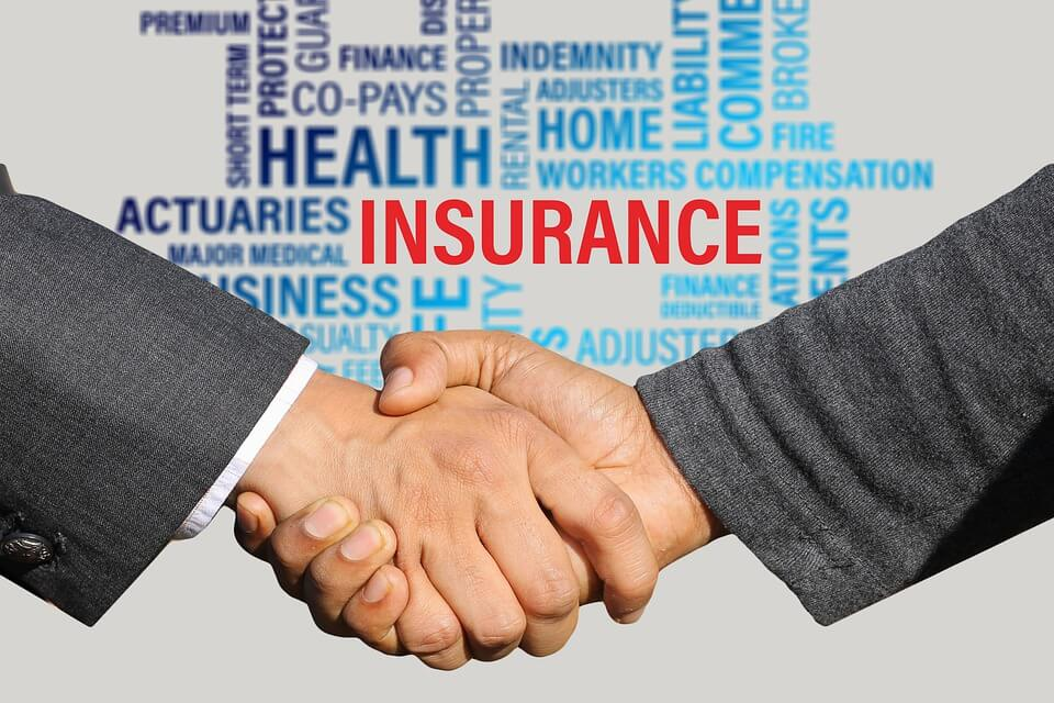 """An image of two people shaking hands and the word """"insurance"""" in red with other related terms, representing how an estate planning attorney from Jenkins Fenstermaker may include long-term care partnership programs as part of your comprehensive estate plan in WV, KY, and OH."""