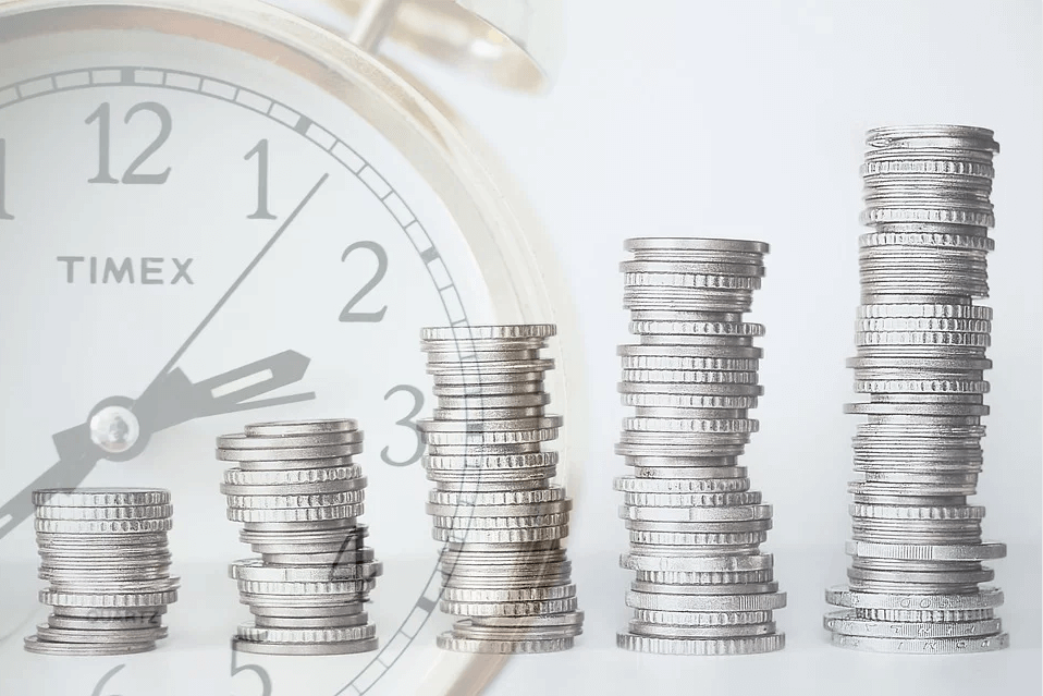 Image of coins stacked in front of a clock, representing what you need to know when putting an IRA in your WV estate plan and how attorney Anna M. Price of Jenkins Fenstermaker, PLLC, can help with estate planning in WV.