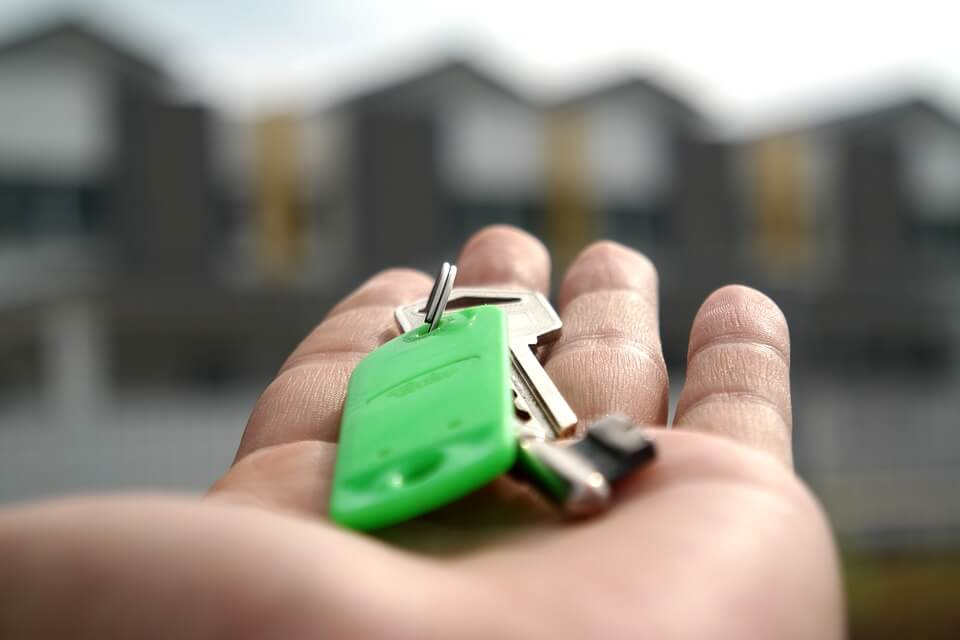 Image of a hand holding house keys, considering a transfer on death (TOD) deed. Talk to experienced estate planning attorney Anna M. Price at Jenkins Fenstermaker to review the pros and cons of transfer on death deeds in WV, KY, and OH.