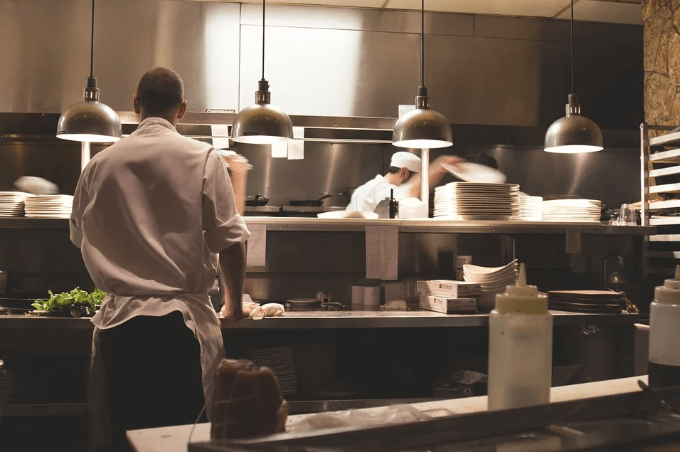 Image of cooks working in a restaurant kitchen, representing how Xavier W. Staggs at Jenkins Fenstermaker, PLLC can answer your restaurant sale questions and facilitate restaurant M&A.