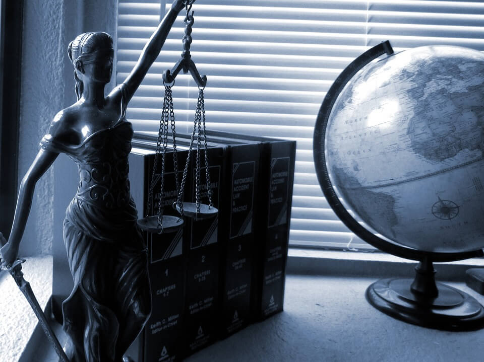 Image of Lady Justice on a shelf next to a globe and code books, representing the legal knowledge and skill that WV municipal defense lawyers need to guide political subdivisions.