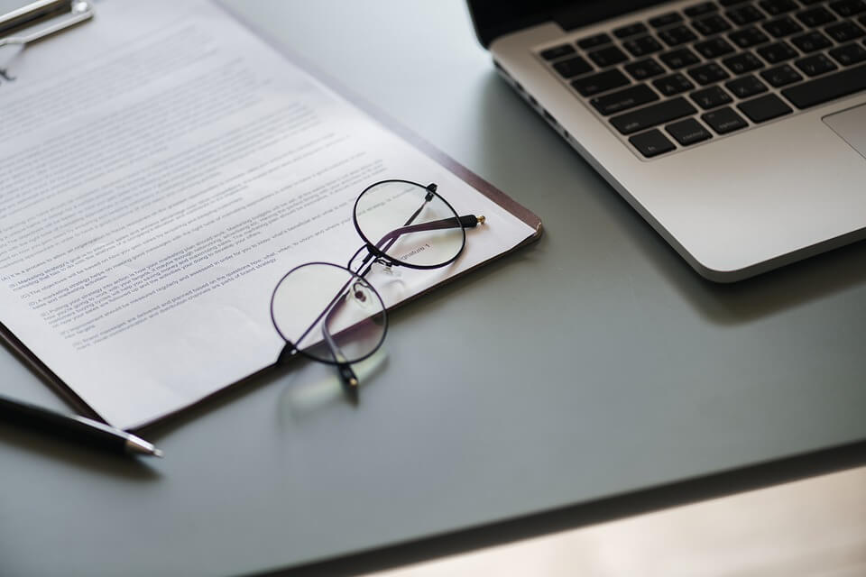 Image of a pair of glasses laying on top of a contract, representing how drafting a WV arbitration clause requires the knowledge and experience of a business lawyer.