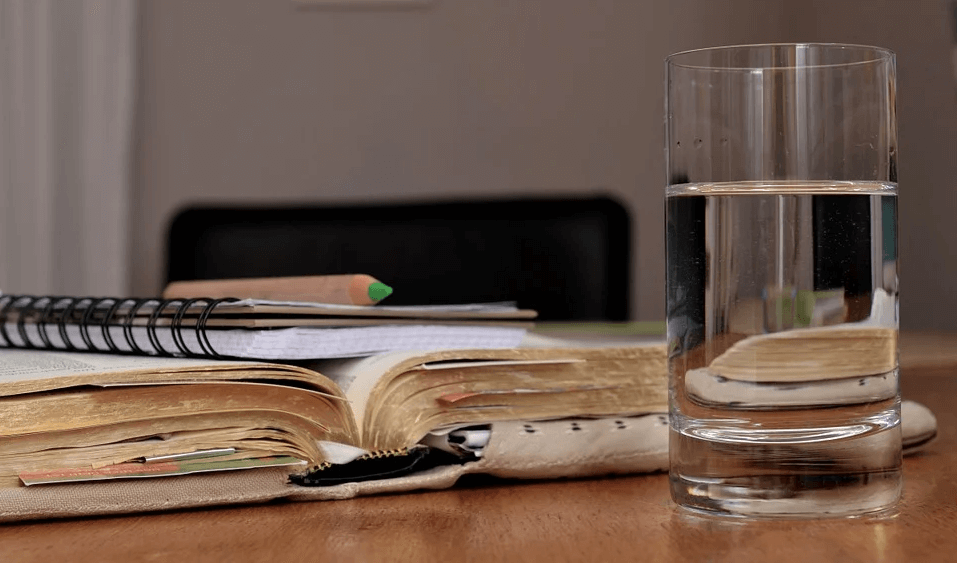 Image of notebooks and a glass of water, representing how Anna M. Price can help non-lawyers identify and perform the duties of an executor in WV, KY, and OH.