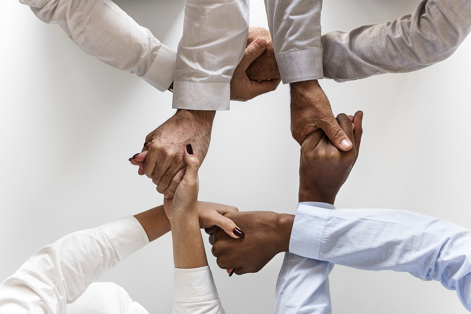 An image of interlinked hands, representing the effective, collaborative approach a business law attorney at Jenkins Fenstermaker will take to help you achieve your specific legal goals.