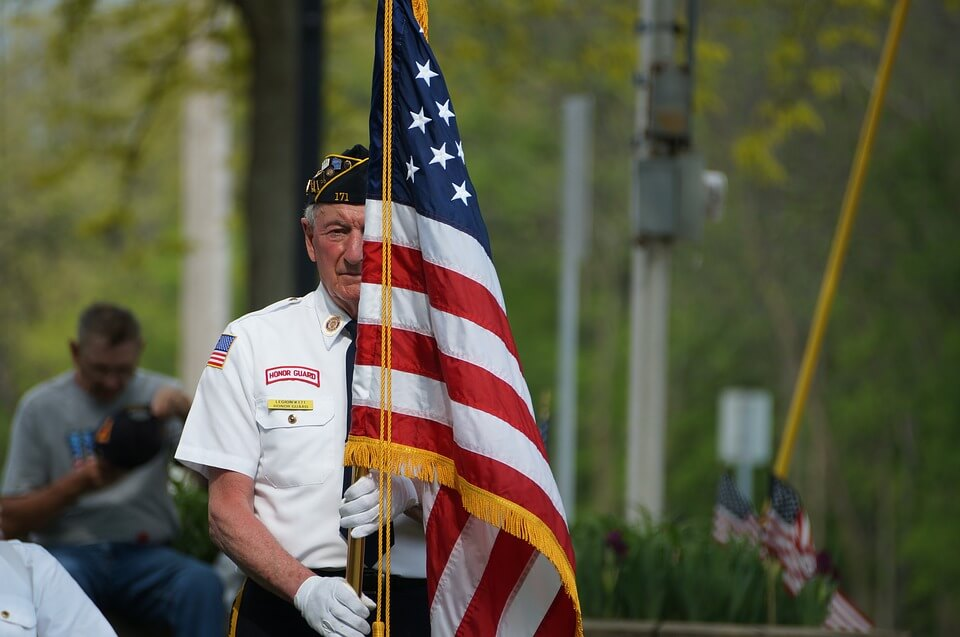 An image of an elderly man in a military uniform holding an American flag, representing those who have served in the US military and the veterans' aid and attendance benefit that might be available to them with the help of an experienced estate planning attorney.