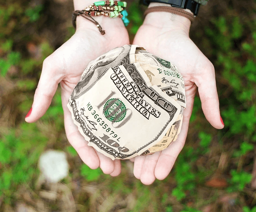 Image of two open hands holding a ball of cash, representing how family foundation attorney Anna M. Price at Jenkins Fenstermaker, PLLC helps those seeking to give back in WV, KY, and OH establish family foundations.