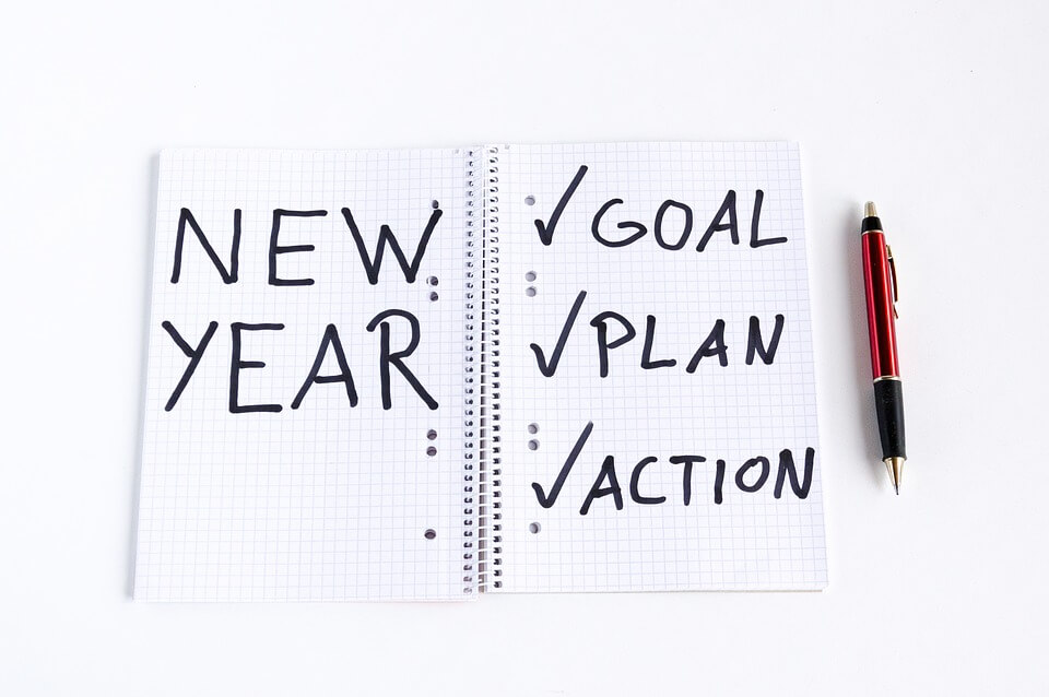 "An image of a notebook with the words ""new year"" and ""goal, plan, action,"" representing the New Year's resolution of setting estate planning goals for the year ahead."