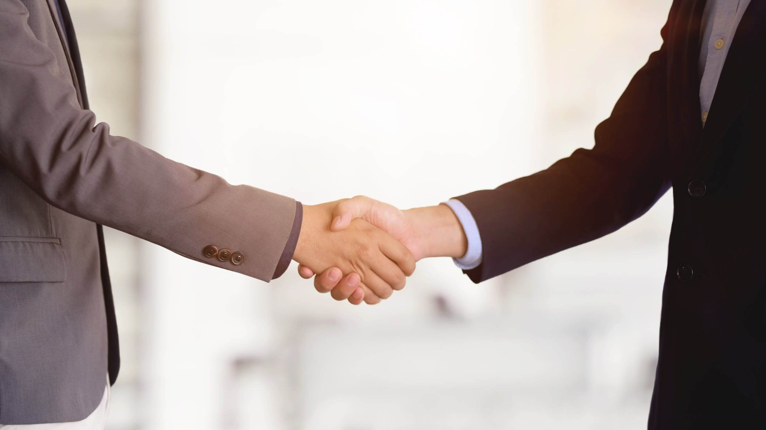 Image of two people shaking hands, representing how M&A lawyer Xavier W. Staggs helps businesses realize the benefits of joining together and understand the the differences between types of mergers.