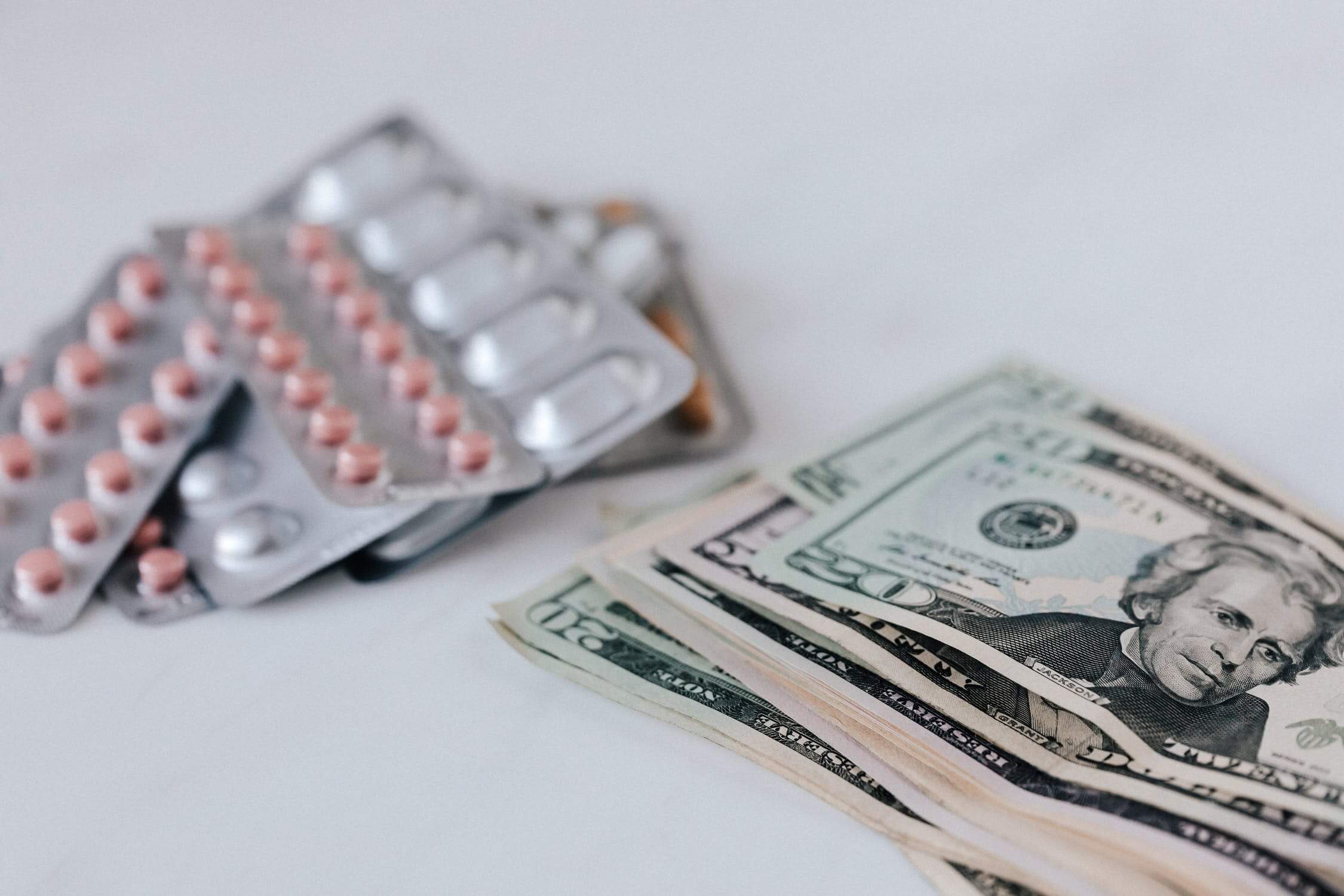 Image of pill-packs and US dollars, representing how employer lawyers at Jenkins Fenstermaker help WV companies navigate FFCRA employer paid leave requirements.
