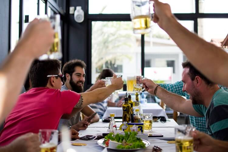 Image of a group of men at a restaurant, representing the restaurant COVID solutions that will persist as customers return to safe dining indoors, as discussed by Huntington business attorney Xavier Staggs.