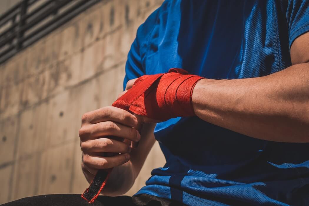 Image of a man wrapping a bandage around his wrist as if in pain, representing how an employer defending appeals under the WV workers' compensation statute of limitations needs experienced counsel such as Steven K. Wellman at Jenkins Fenstermaker, PLLC.