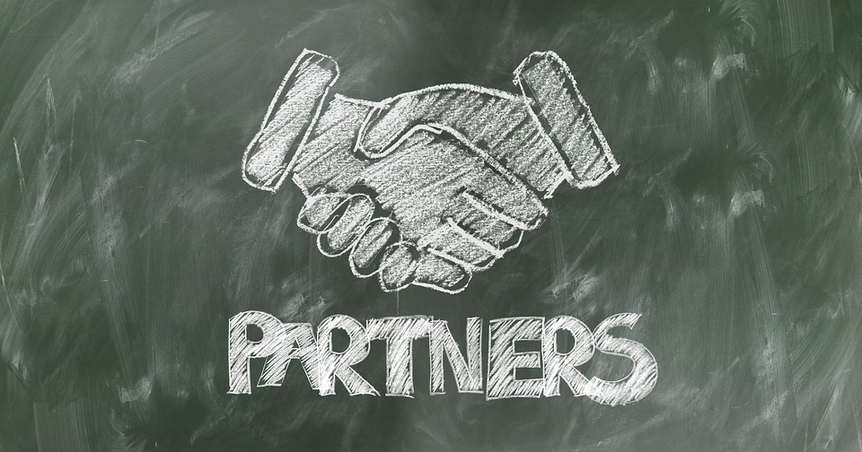 "A chalk image of shaking hands and the word ""partners"" written on a chalkboard, representing the partnership out-of-state attorneys can form with a WV local counsel from Jenkins Fenstermaker in West Virginia."
