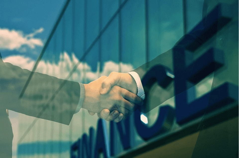 Image of two businesspeople shaking hands in front of an office building in a merger or acquisition, representing how M&A attorney Xavier W. Staggs helps businesses create and execute a successful M&A plan.