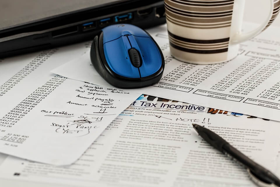 Image of paperwork with tax calculations, a computer mouse, and inkpen, representing an employee completing the new I-9 form in WV.