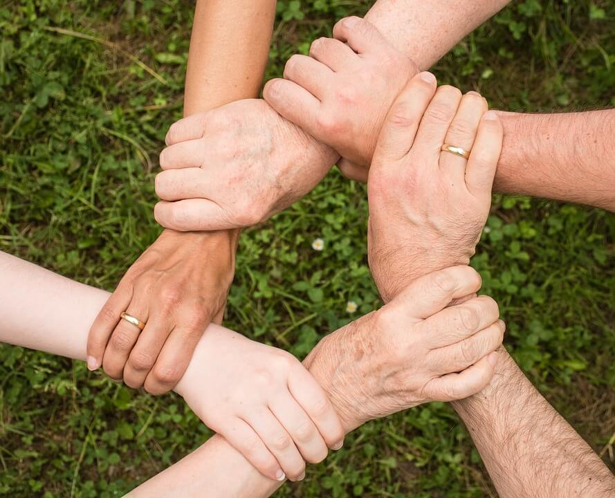 An image of an interlocked circle of hands, representing the need for communicating your estate plan to help your family understand your true wishes and prevent disputes during the settlement of your estate.