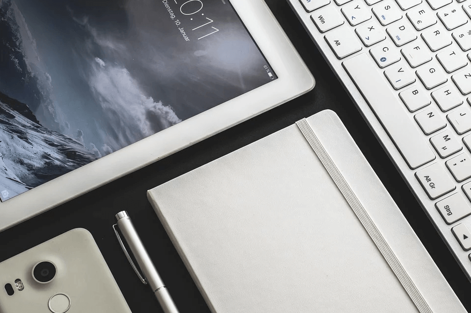 Image of a tablet, cell phone, notebook, and keyboard, representing the need to discuss a digital property estate plan with a knowledgeable attorney who can help you determine how to protect your digital assets if a tragedy occurs.