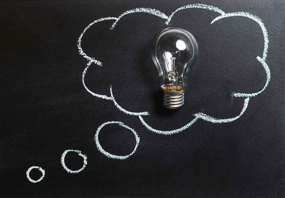 Image of a chalkboard displaying a light bulb surrounded by a cloud, symbolizing thinking about all potential outcomes of a business ownership transition in WV, KY, or OH.