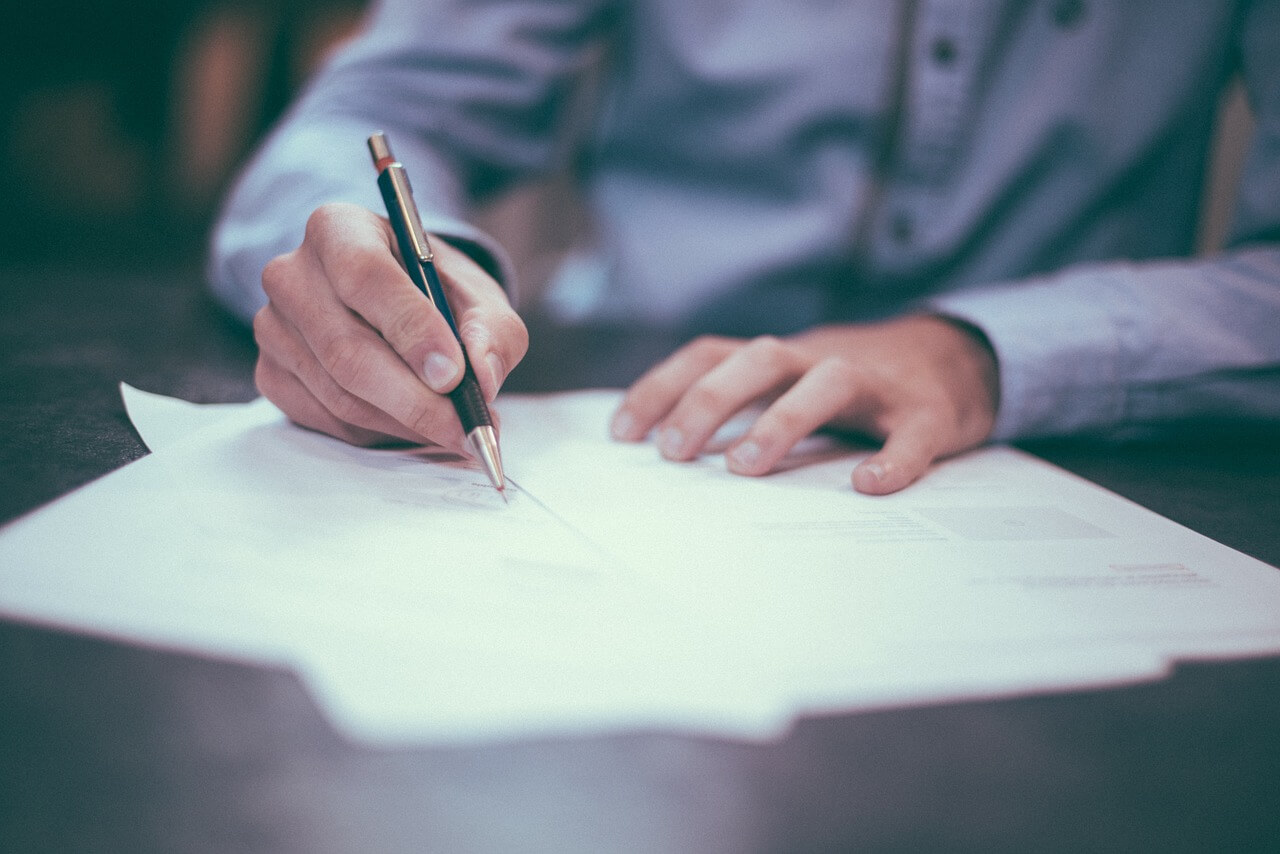 An image of hands signing a document that is out of focus, representing the need for clarifying the intent of the deceased in WV undue influence will and trust cases with the help of an attorney.