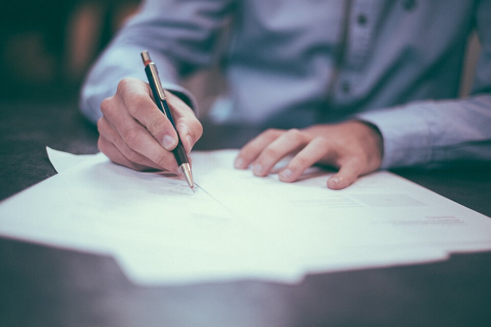 Image of a man signing an Ohio power of attorney, representing one of the many comprehensive estate planning services offered by Anna M. Price of Jenkins Fenstermaker.