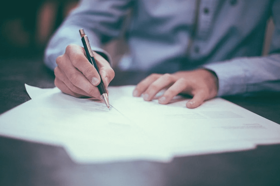 Image of a client signing trust documents, representing a person who worked with a trust lawyer in WV to determine the best trust documents to complete their estate plan.